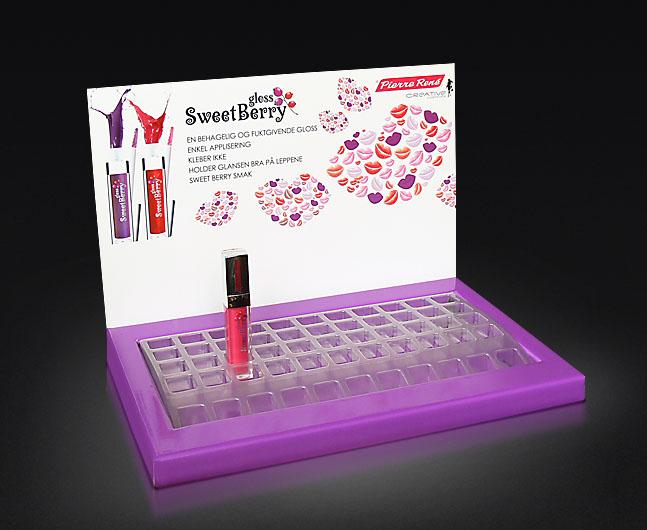 Ekspozytor naladowy do kosmetyków z toperem, do ekspozycji produktów jest wykorzystany blistr z tworzywa.